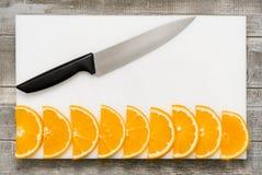 Fette arancio impilate su un bordo bianco, coltello fotografia stock libera da diritti