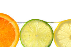 Fette arancioni della limetta e del limone in acqua Fotografie Stock Libere da Diritti