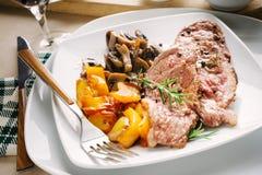 Fette arrostite della carne con i funghi del fungo prataiolo ed i peperoni gialli Fotografie Stock
