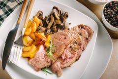 Fette arrostite della carne con i funghi del fungo prataiolo ed i peperoni gialli Immagini Stock