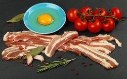 Fette crude del bacon, tuorlo d'uovo, pomodoro sul bordo nero Fotografia Stock Libera da Diritti