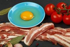 Fette crude del bacon, tuorlo d'uovo, pomodoro sul bordo nero Immagine Stock