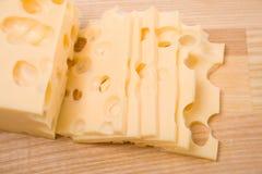 Fette del formaggio sulla scheda di taglio Fotografia Stock Libera da Diritti