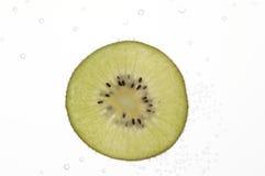 Fette del kiwi in acqua con le bolle Immagini Stock