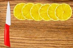 Fette del limone e del coltello sul tagliere Fotografie Stock