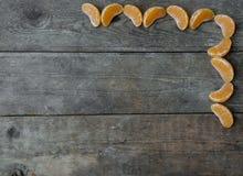 Fette del mandarino su fondo di legno Fotografia Stock