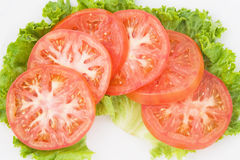 Fette del pomodoro su verde Fotografia Stock Libera da Diritti
