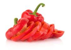 Fette del primo piano di peperoni dolci rossi su bianco con le gocce di acqua Fotografie Stock
