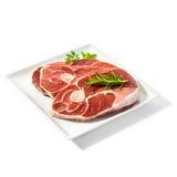 Fette dell'agnello sul piatto con le erbe della spezia Fotografia Stock