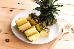 Fette dell'ananas sul piatto bianco sul legno Immagine Stock
