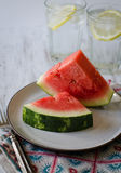 Fette dell'anguria sul piatto con acqua ghiacciata nel fondo Immagini Stock