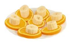 Fette della banana e dell'arancio su una zolla Fotografia Stock Libera da Diritti