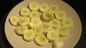 Fette della banana su un piatto beige girare su un fondo nero stock footage