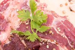 Fette della carne del manzo ed aglio crudi freschi, pepe su di legno Fotografia Stock