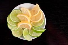 Fette della limetta e del limone sulla tabella di legno nera. Immagini Stock