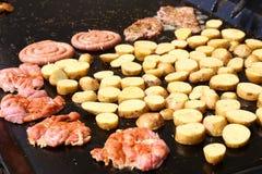 Fette della patata e della carne di maiale in pentola Immagine Stock