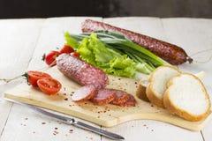 Fette della salsiccia, pomodoro, lattuga, pane su un bordo di scultura di legno Fotografie Stock Libere da Diritti