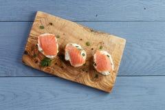 Fette delle baguette con formaggio a pasta molle ed il salmone sopra Fotografie Stock