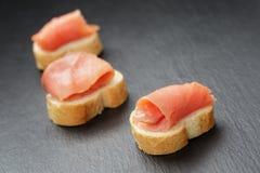 Fette delle baguette con il salmone curred sull'ardesia Fotografie Stock