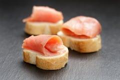 Fette delle baguette con il salmone curred sull'ardesia Immagine Stock