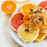 Fette di agrume con Granola su un piatto Fotografia Stock Libera da Diritti