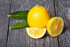 Fette di agrume e di intero limone con le foglie su superficie di legno Fotografia Stock Libera da Diritti