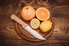Fette di agrume organico fresco con il coltello sul bordo di legno Fotografia Stock Libera da Diritti