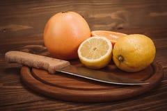 Fette di agrume organico fresco con il coltello sul bordo di legno Immagini Stock Libere da Diritti