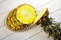 Fette di ananas maturo in un piatto trasparente su un diago bianco immagine stock libera da diritti