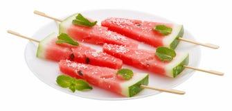 Fette di anguria con il bastone sul piatto bianco su bianco Fotografia Stock Libera da Diritti