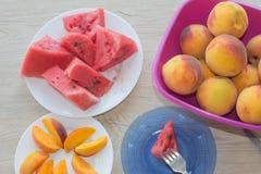 Fette di anguria e di pesche su un piatto sulla tavola di legno L'anguria e le pesche senza semi mature organiche incidono i cune fotografie stock