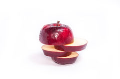 Fette di Apple nel rosso su fondo bianco. immagine stock