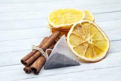 Fette di arancia con la bustina di tè e della cannella su un fondo di legno leggero, godenti delle spezie fotografia stock