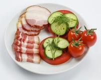 Fette di bacon con i pomodori ed i cetrioli su fondo bianco Fotografia Stock