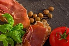 Fette di baguette alpine casalinghe fresche con jamon, basilico, oliv Immagine Stock