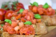 Fette di baguette tostate con il pomodoro - Bruschetta - macro colpo Fotografie Stock Libere da Diritti
