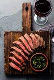 Fette di bistecca rara media del manzo sul bordo di legno, vetro di vino rosso immagine stock libera da diritti