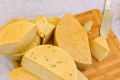 Fette di bugia del formaggio su un primo piano del bordo di legno Tipi differenti di formaggio, di tovaglia di tela bianca e di c immagini stock