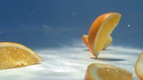 Fette di caduta arancio sulla tavola bianca stock footage