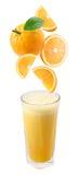Fette di caduta arancione in un vetro di spremuta fresca. Fotografie Stock