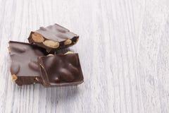 Fette di cioccolato fondente con i dadi su una tavola di legno bianca immagini stock