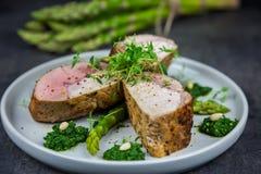 Fette di filetto arrostito della carne di maiale su asparago con il pesto da cavolo e da timo sul piatto bianco Immagine Stock Libera da Diritti