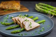 Fette di filetto arrostito della carne di maiale su asparago con il pesto da cavolo e da timo sul piatto grigio Immagine Stock