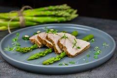 Fette di filetto arrostito della carne di maiale su asparago con il pesto da cavolo e da timo sul piatto grigio Immagine Stock Libera da Diritti