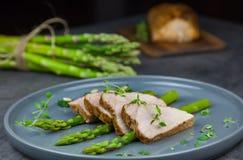 Fette di filetto arrostito della carne di maiale su asparago con il pesto da cavolo e da timo sul piatto grigio Immagini Stock Libere da Diritti