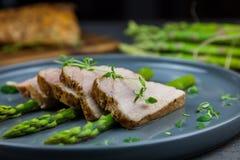 Fette di filetto arrostito della carne di maiale su asparago con il pesto da cavolo e da timo sul piatto grigio Immagini Stock