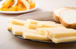 Fette di formaggio e di pane su un primo piano del piatto Immagine Stock Libera da Diritti