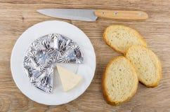 Fette di formaggio fuso in piatto, pezzi di pane Fotografia Stock