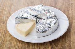 Fette di formaggio fuso in stagnola in piatto bianco Fotografia Stock