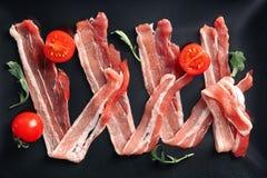 Fette di lardo di bacon su fondo nero immagini stock